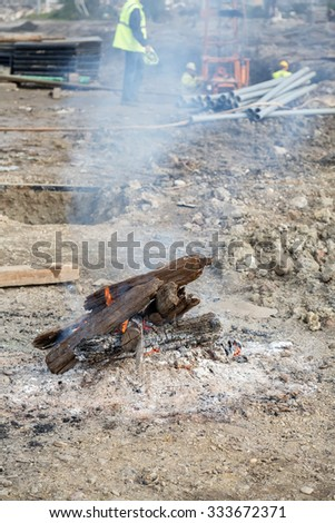 Bonfire for workers at the construction site. Frosty concept. During break, workers sit around a bonfire to warm themselves.  - stock photo