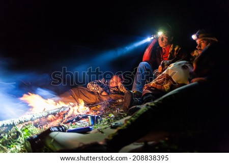 Bonfire in a camp in the mountains and the light of flashlights - stock photo