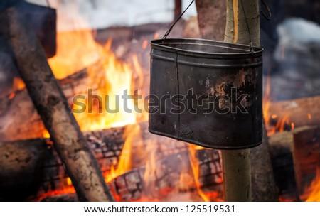 Bonfire with metal black kettle - stock photo