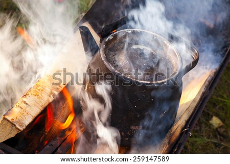 Bonfire with smoke over metal old black boiling teapot  - stock photo