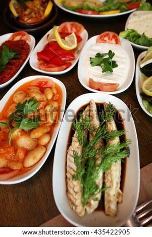 Bonito fish with Turkish appetizer food on the restaurant table. - stock photo