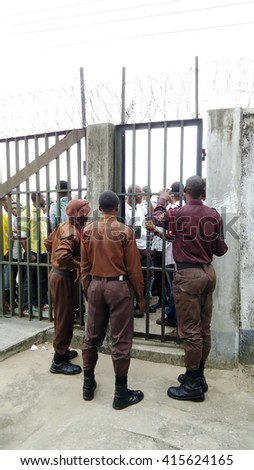BONNY ISLAND, NIGERIA - APRIL 5, 2013: People wait outside the gate at a vocational center to take a test for an oil company job fair, with police waiting inside - stock photo