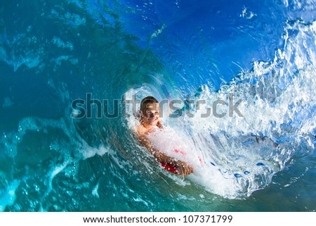 Boogie boarder surfing a wave, riding in the tube or barrel
