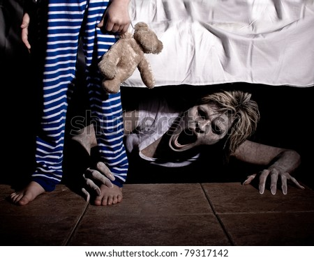 Boogie Man under the Bed Scaring a Young Child - stock photo