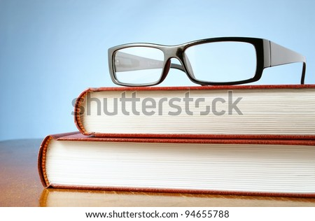 book and black-rimmed glasses on a table - stock photo