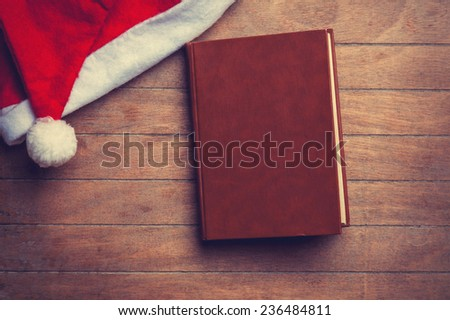Book and christmas hat on wooden table. - stock photo