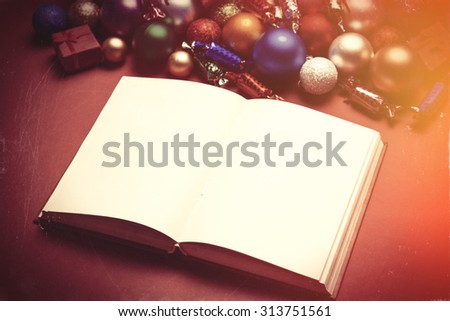Book and chritmas toys on white background.