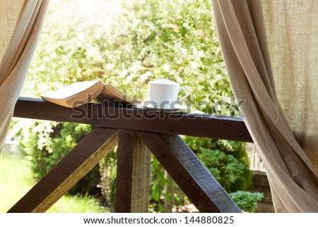 Book and coffee in the garden terrace - peaceful weekend morning concept - stock photo