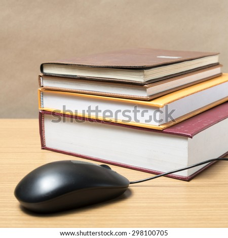 book and computer mouse on wood background