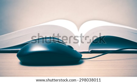 book and computer mouse on wood background vintage style - stock photo