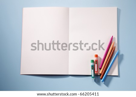 Book and crayons isolated on the blue background. - stock photo
