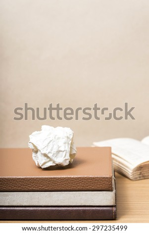 book and crumpled paper on wood background