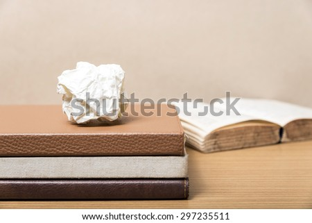 book and crumpled paper on wood background - stock photo
