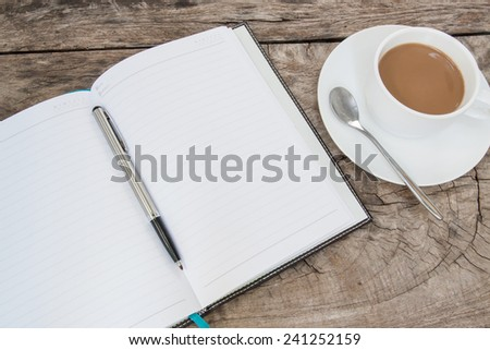 book and cup of coffee on wood table - stock photo