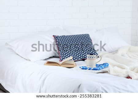 Book and cup of tea on bed close-up - stock photo