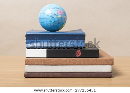 book and earth ball on wood background - stock photo