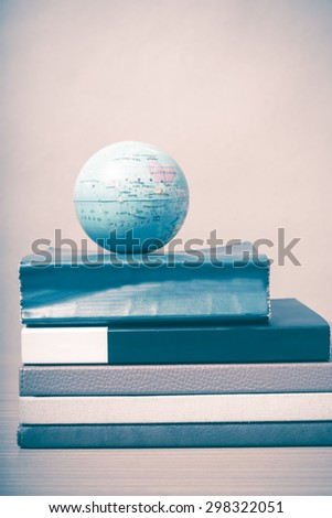 book and earth ball on wood background vintage style - stock photo