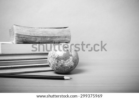 book and earth ball with black pencil on wood background black and white color tone style - stock photo