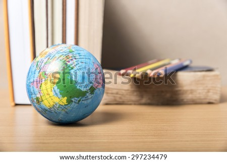 book and earth ball with color pencil on wood background - stock photo