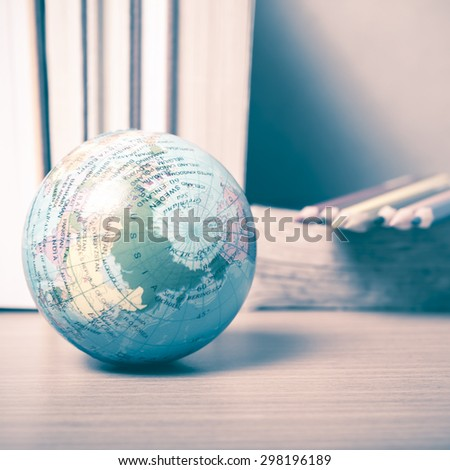 book and earth ball with color pencil on wood background vintage style