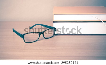 book and eyeglasses on wood background vintage style