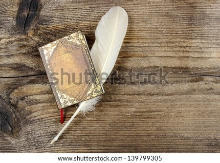 Book and feather on wooden rough background. Copy space.