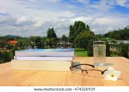 book and glass on wooden platform , selective focus