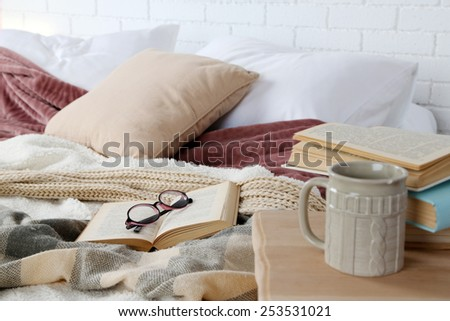 Book and glasses on bed close-up - stock photo