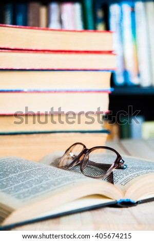 book and glasses on table in library close up