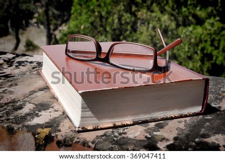 book and glasses on the wall outdoors - stock photo