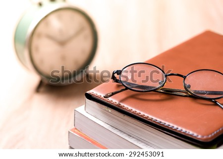 book and glasses on wood table