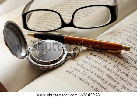Book and glasses with pen and pocket watch - stock photo
