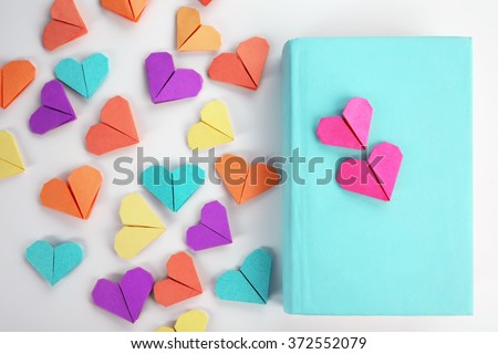 Book and heart shaped bookmark on a light wooden background - stock photo