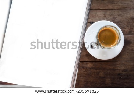 Book and hot coffee on a wooden table