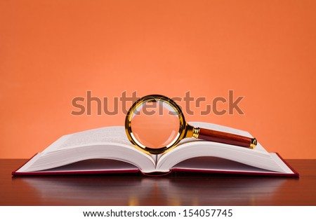 book and magnifying glass on table - stock photo