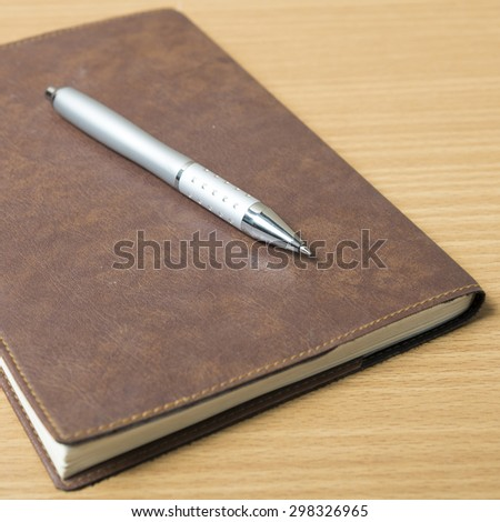 book and pen on wood background