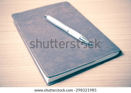 book and pen on wood background vintage style