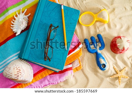 Book and reading glasses on a colorful beach towel on a sandy beach with kids plastic toys, a starfish and seashells conceptual of a tropical summer vacation - stock photo