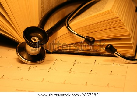 Book and stethoscope on a EKG printout - stock photo