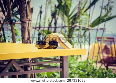 Book and sunglasses lying on a yellow table in a tropical beach cafe. Vacation theme concept - stock photo
