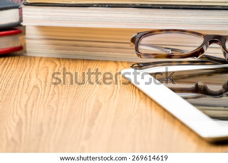 Book and tablet on wooden table.education