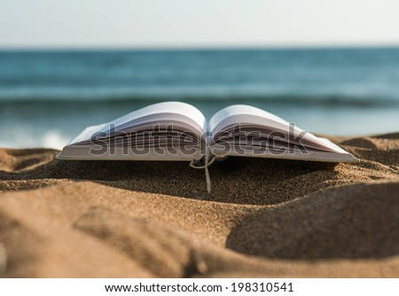 Book at beach during summer by the sea at sunset