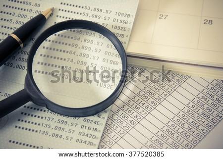 Book bank, Magnifier, Calendar, a ball pen. Vintage filter effect. - stock photo