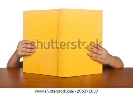 Book blocking the face of a child while reading it  - stock photo