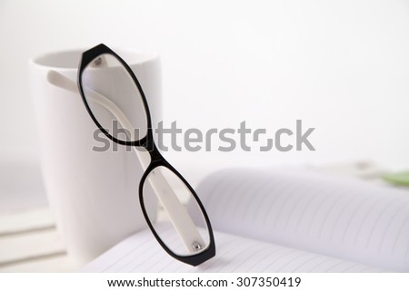 Book ,glasses and cup on the table in white background
