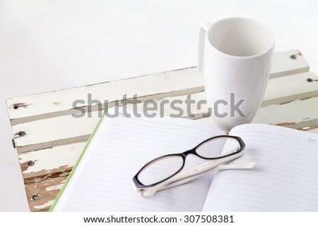 Book ,glasses and cup on the table in white background - stock photo