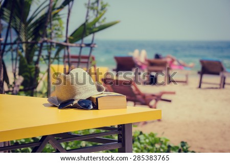 Book, hat and sunglasses, lying on a yellow table in a tropical beach cafe. Vacation theme concept - stock photo