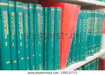 Book in a bookshelf standing out at university library. Selective focus - stock photo
