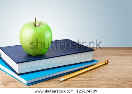 Book, notebook with apples and pencil on table - stock photo