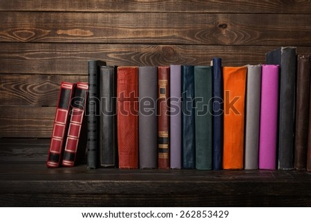 Book. Old books on a wooden shelf. No labels, blank spine.  - stock photo